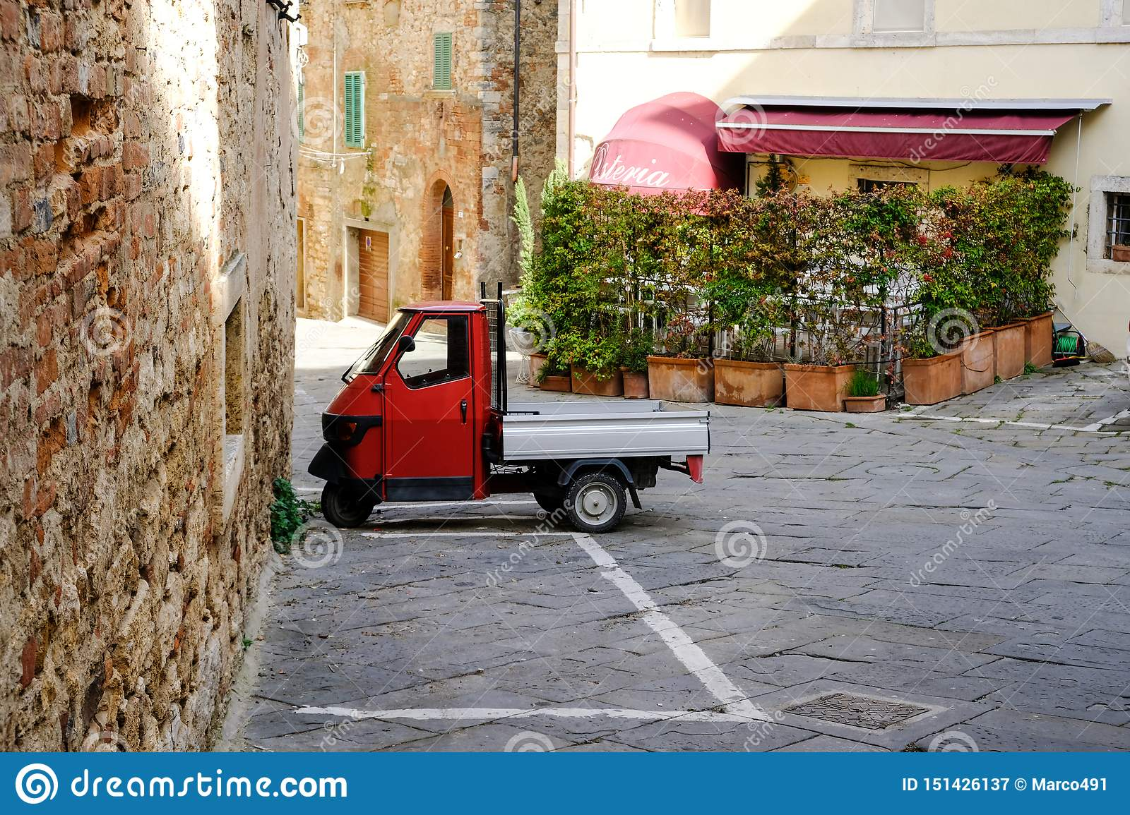 Rapolano Terme, Tuscany, Italy. Ape PIaggio red parked in the old town