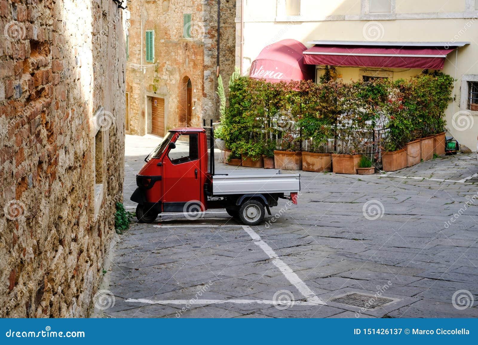 Rapolano Terme, Tuscany, Włochy Małpuje Piaggio czerwień parkującą w starym miasteczku