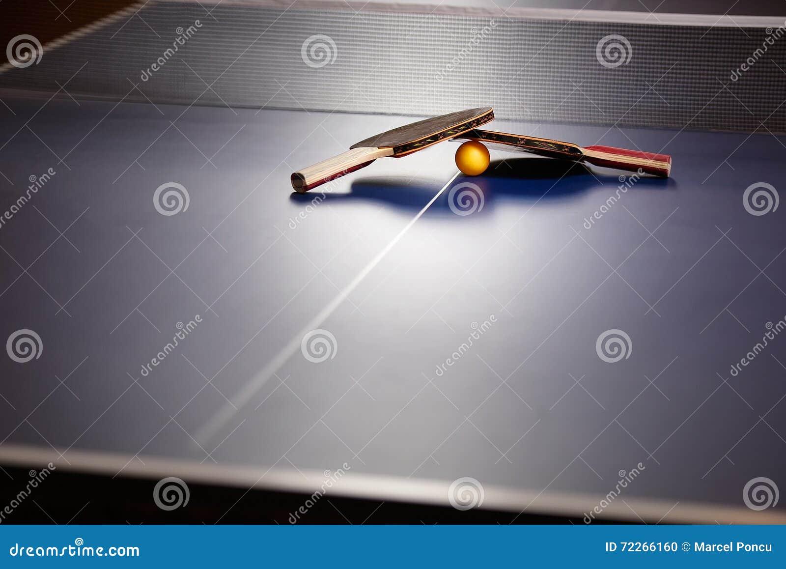 Raquetes e bola do pong do tênis de mesa dois ou do sibilo em uma tabela azul w
