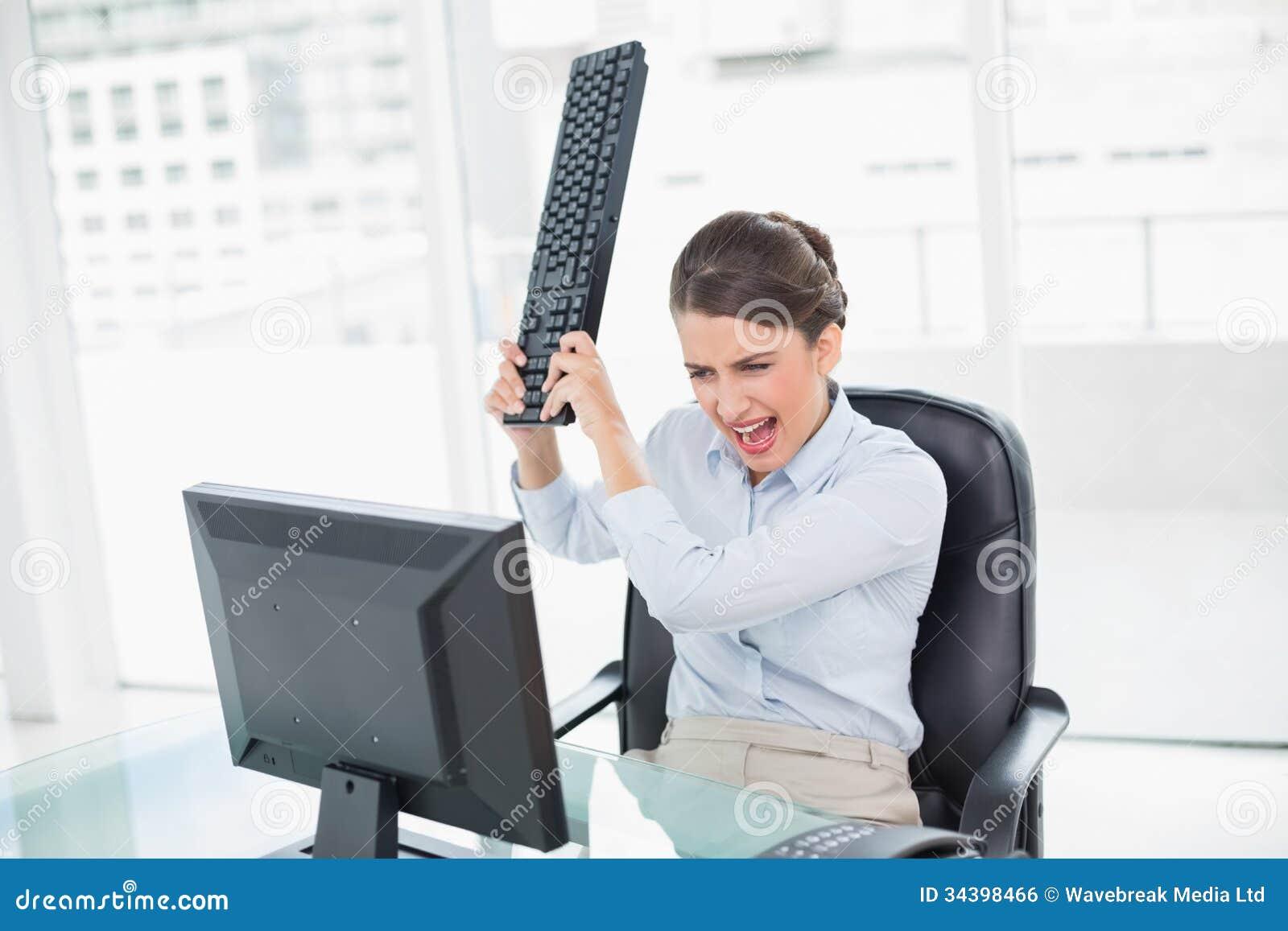 Rasande flott brun haired affärskvinna som kastar hennes tangentbord på hennes dator