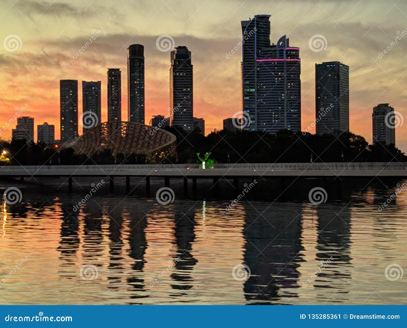 Rascacielos cerca del agua contra el sol poniente