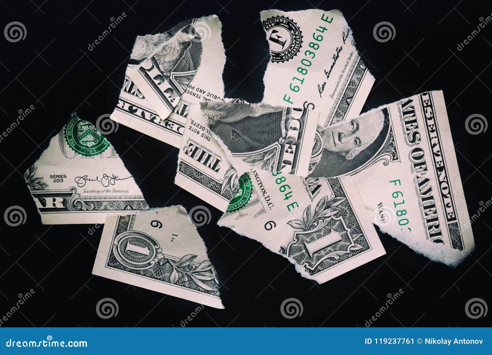 Rasgado rasgó devaluado un billete de banco del dólar en un fondo negro