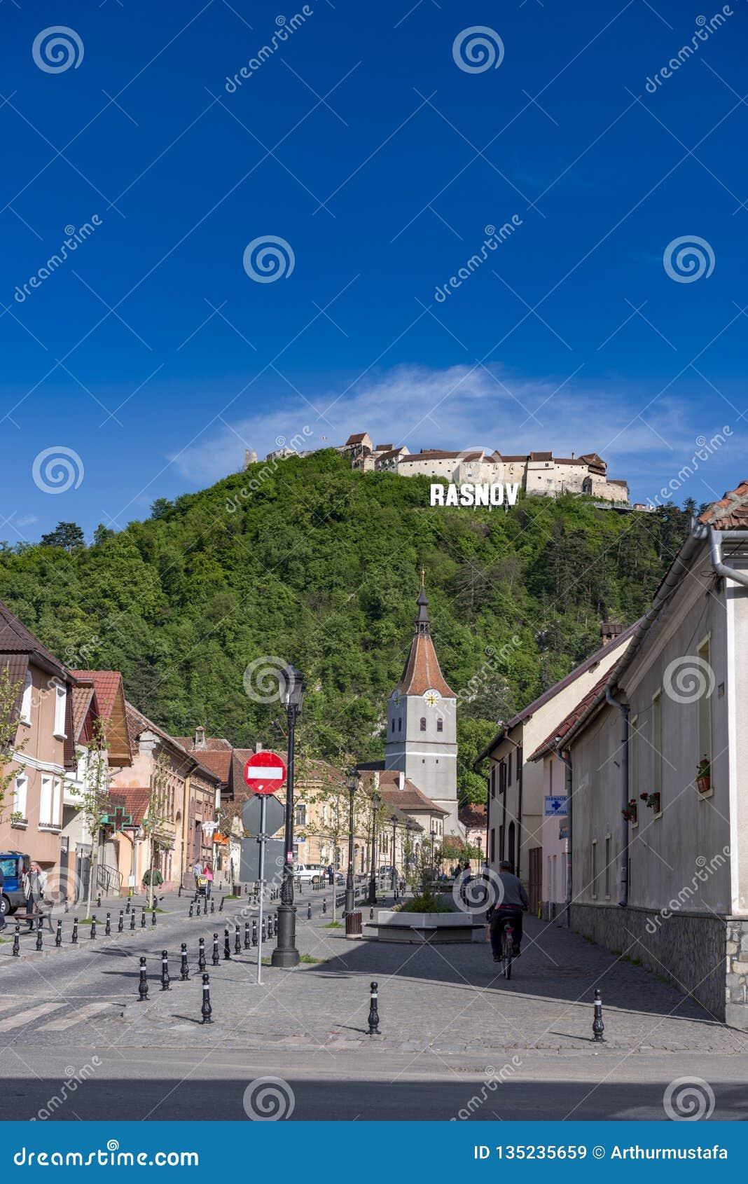 Rasnov, Румыния - май 2017: Взгляд mainstreet города Rasnov (графства Brasov (Румынии), с холмом средневекового Rasnov