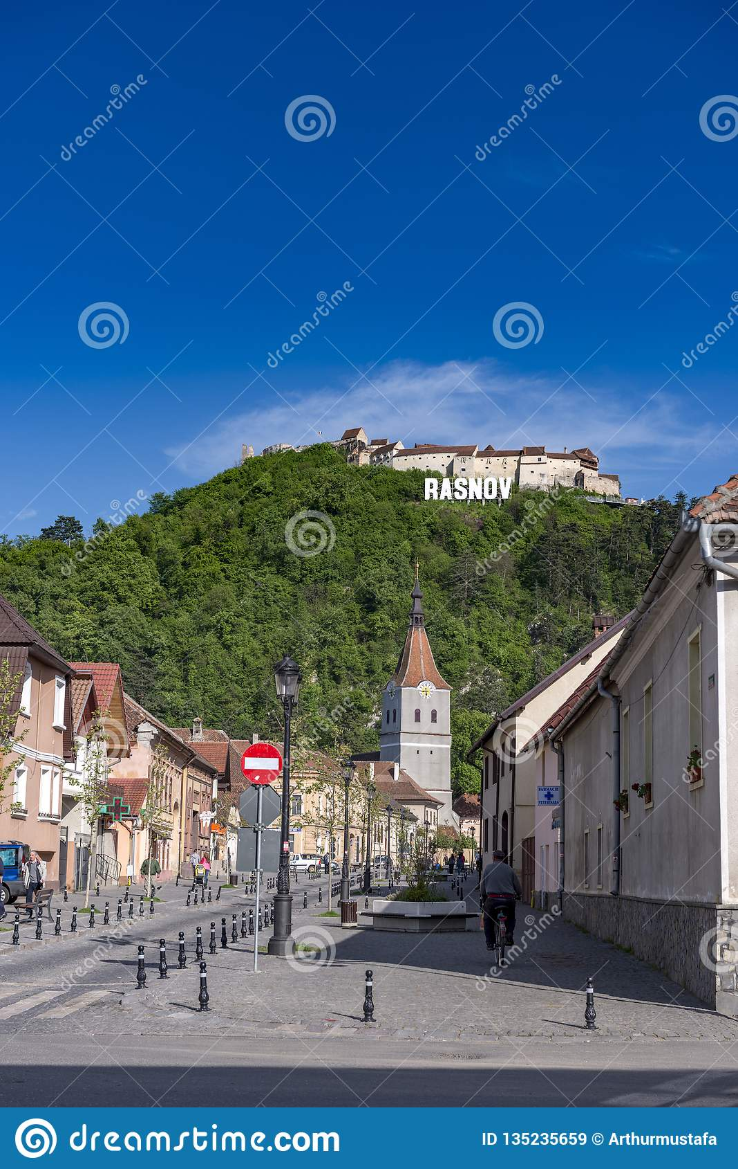 Rasnov Rumänien - Maj, 2017: Sikt av den Rasnov stadsmainstreeten (det Brasov länet (Rumänien), med kullen av den medeltida Rasno