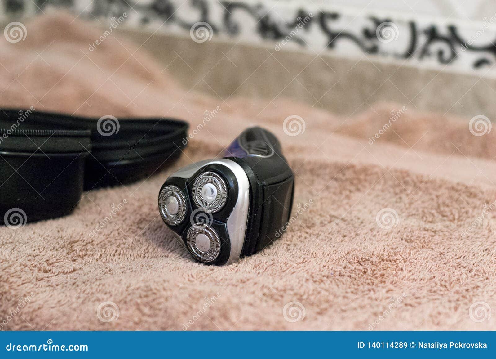 Rasoir rotatoire bleu électrique avec trois lames près des serviettes noires de cas et de bain