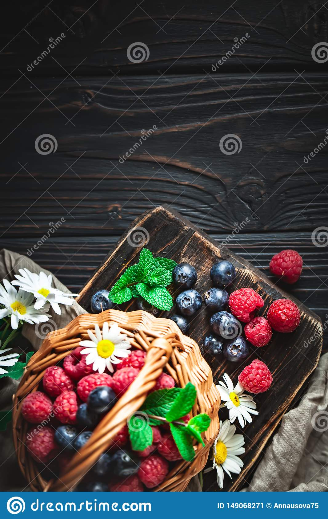 Raspberries and blueberries in a basket with chamomile and leaves on a dark background. Summer and healthy food concept