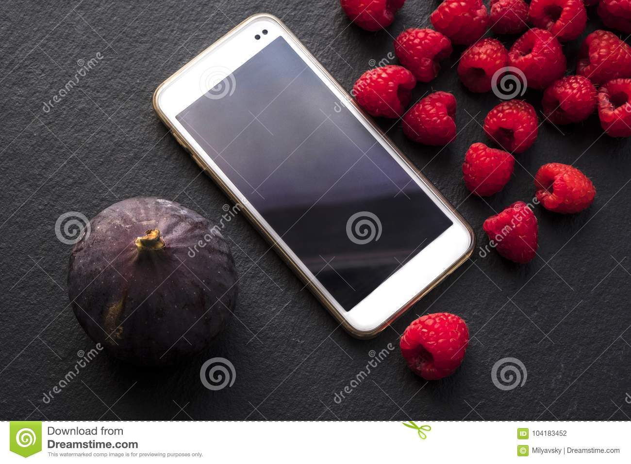 Raspberries, figs and gadget on black shale