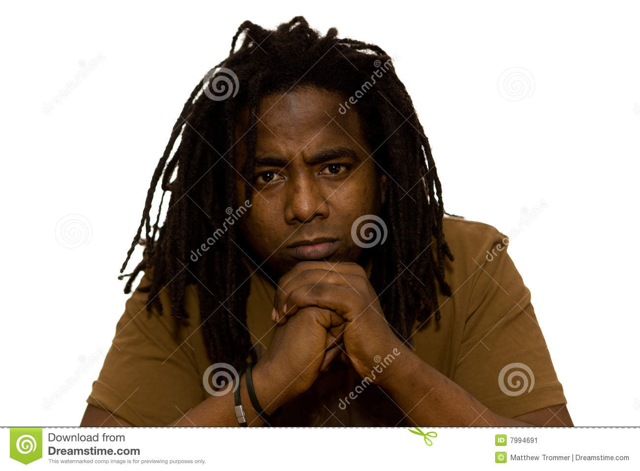 Serious African adult male with dreadlocks sitting in thought on a ...