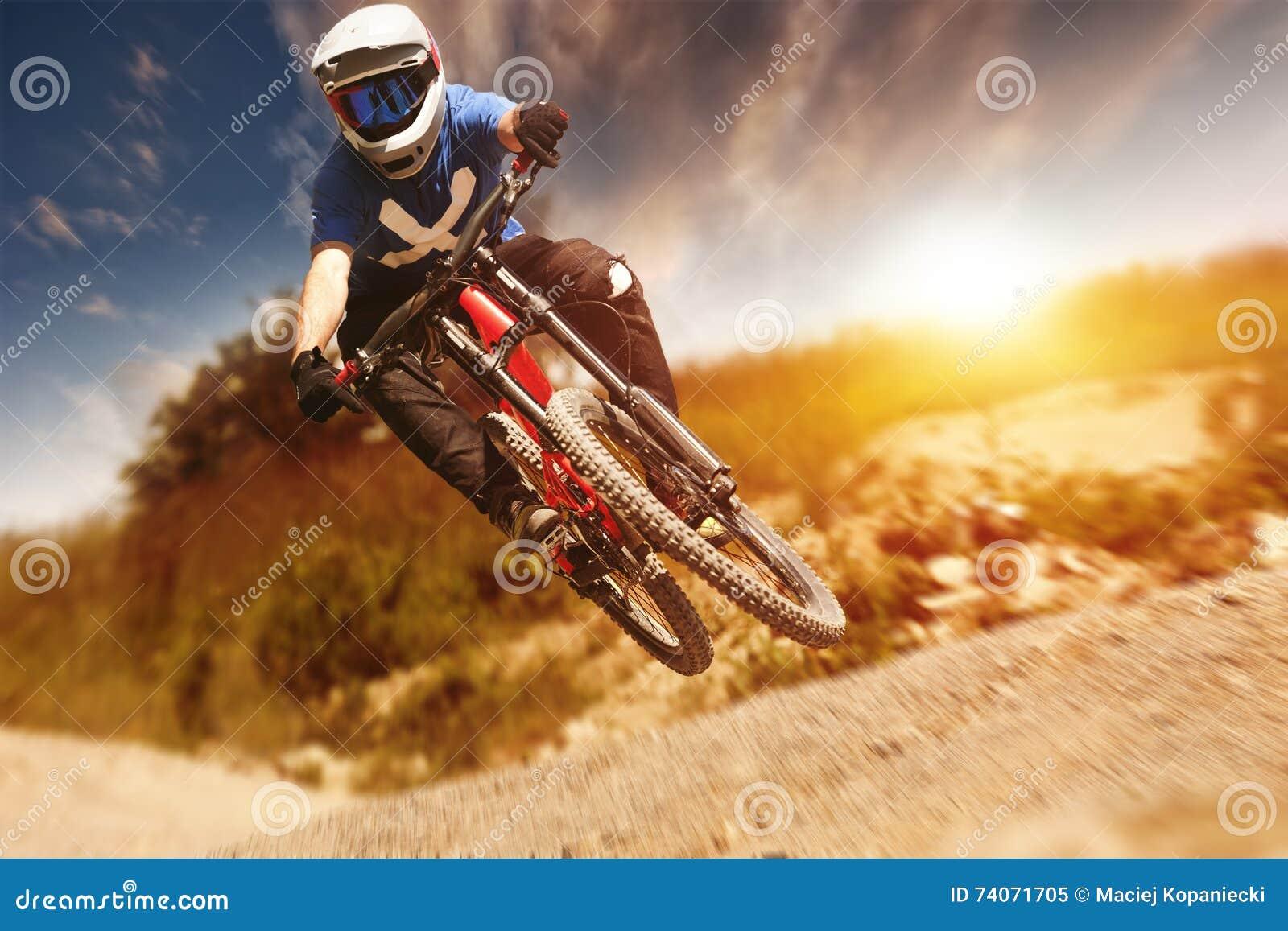 Rastro de la puesta del sol de Mountainbiker cuesta abajo