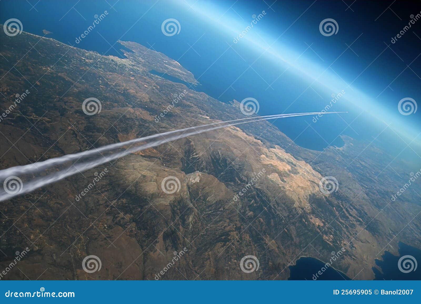 Rastro del aeroplano sobre la tierra de la mañana.
