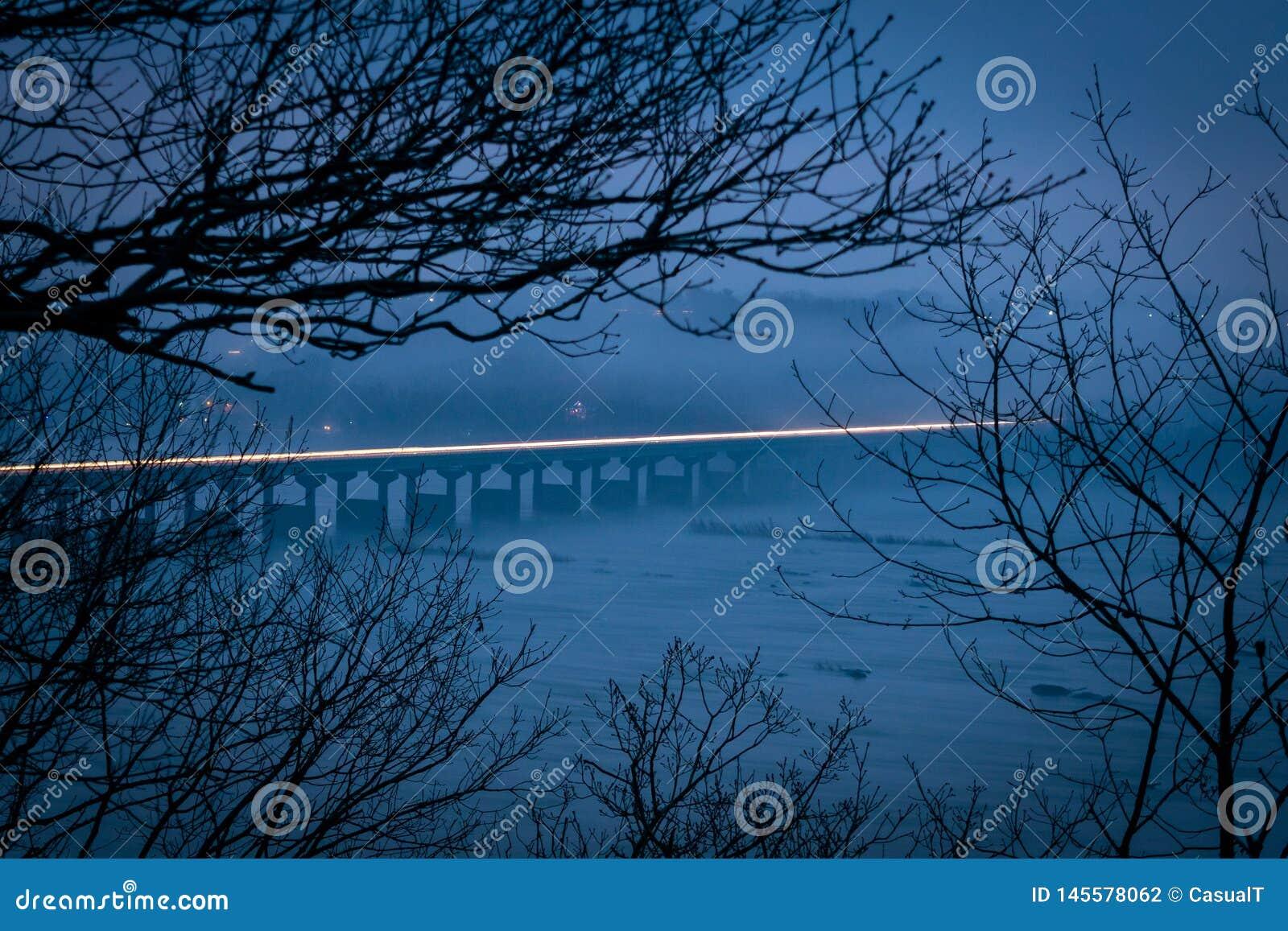 Rastro ligero a través del puente del río Susquehanna, sobre las horas de igualación en un día brumoso y de niebla, el condado de