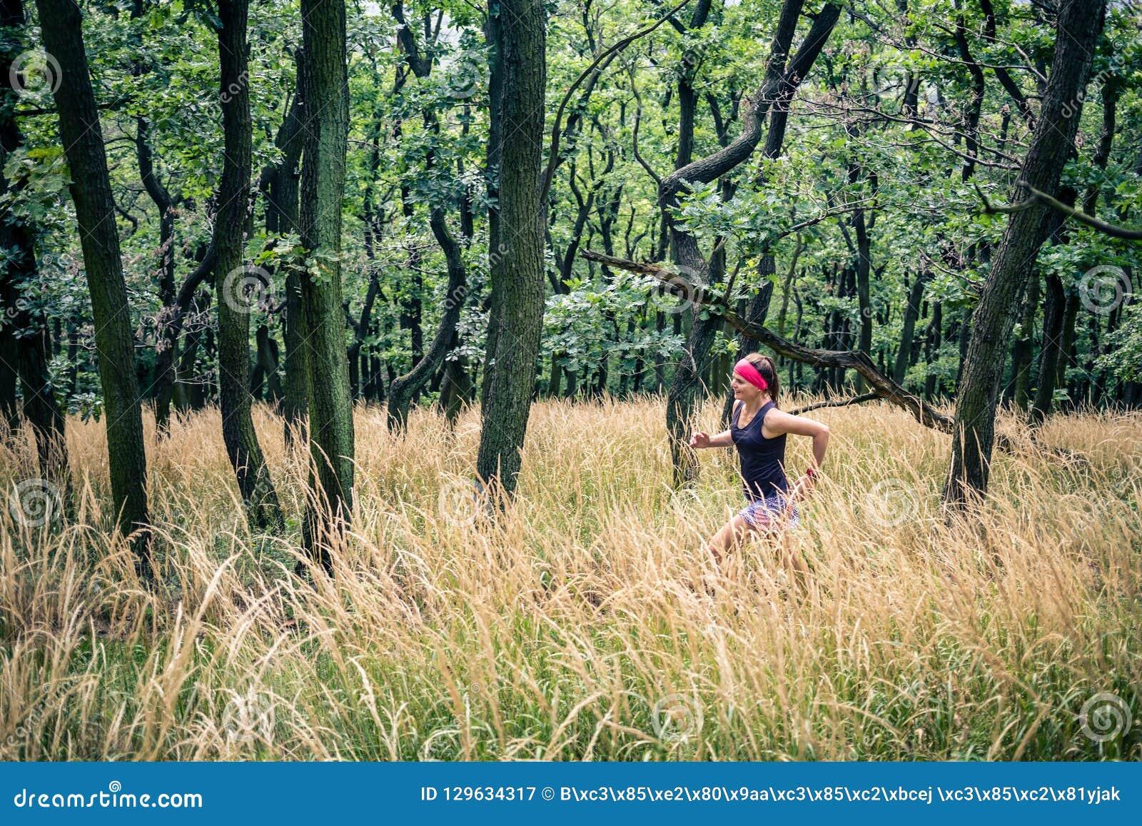 Rastro que funciona con a la mujer atlética en el bosque verde, inspiración de los deportes