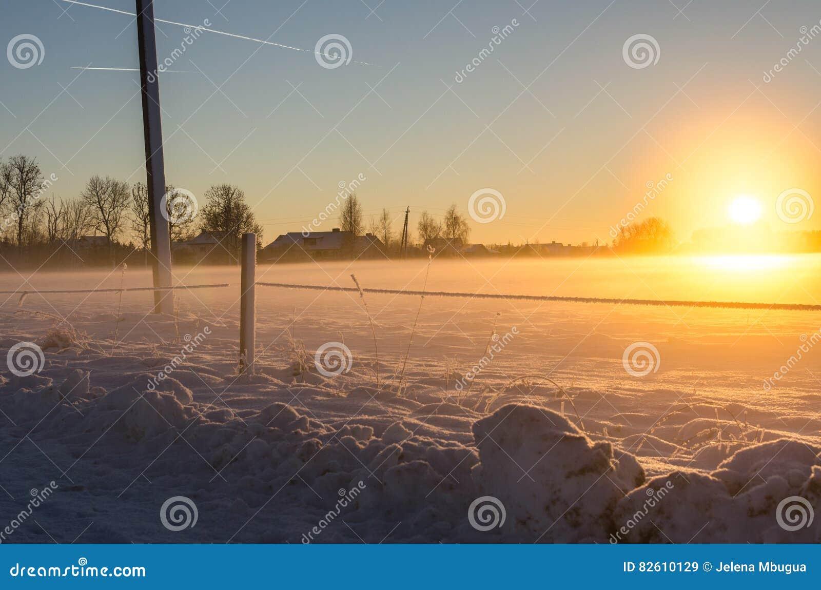 Rastros del jet y una puesta del sol de oro en un campo nevoso