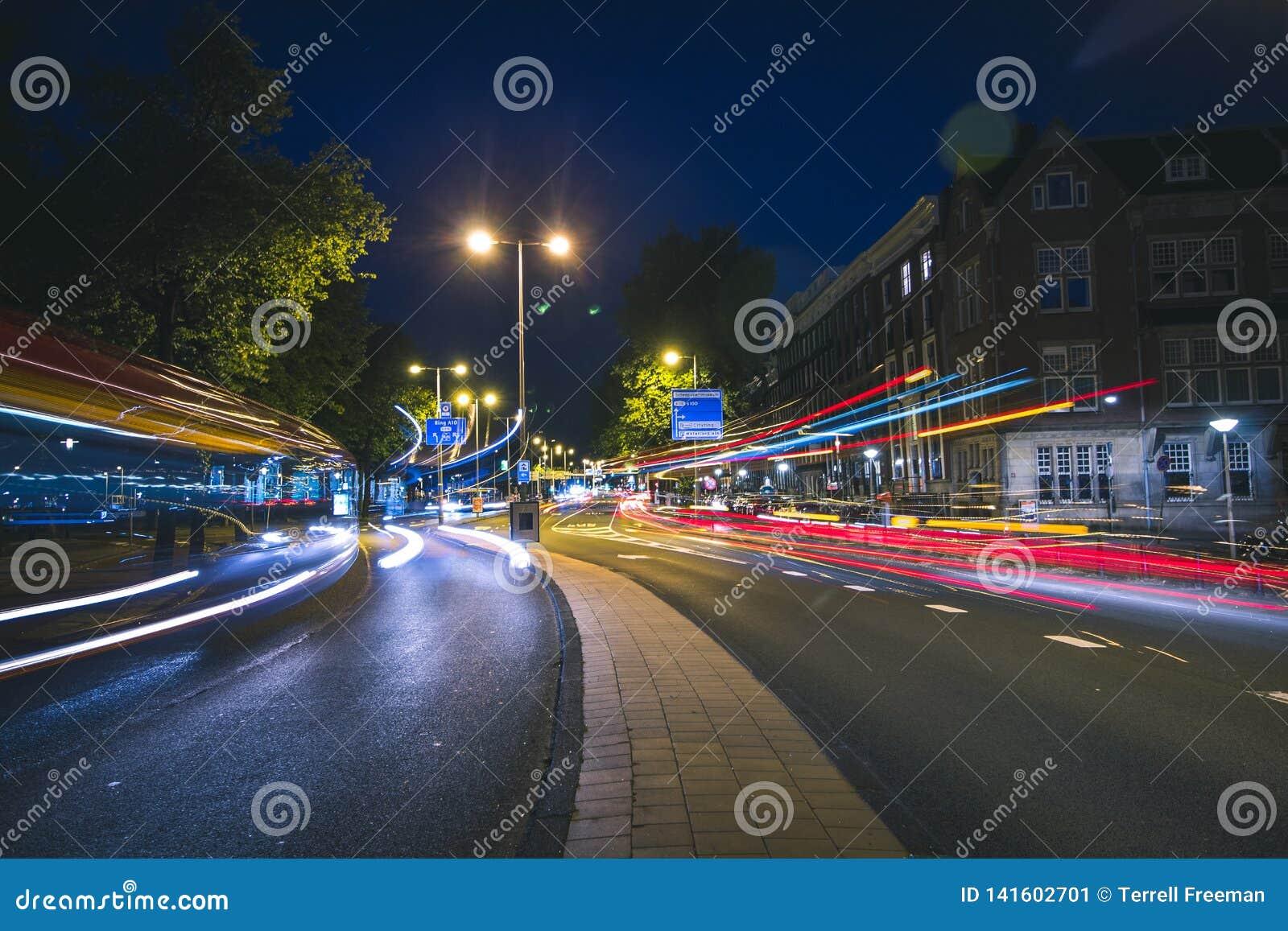 Rastros ligeros de autobuses y del tráfico en Amsterdam, Países Bajos