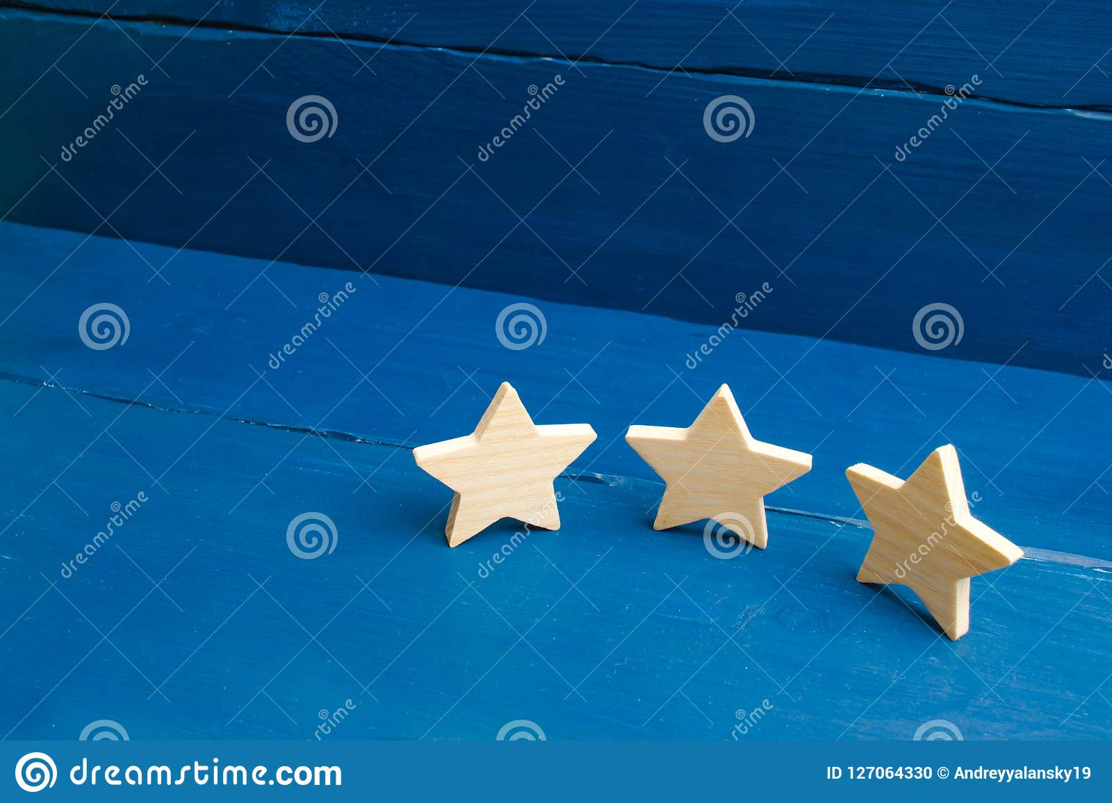 The rating of the hotel, restaurant, mobile application. Three stars on a blue background. The concept of rating and evaluation.