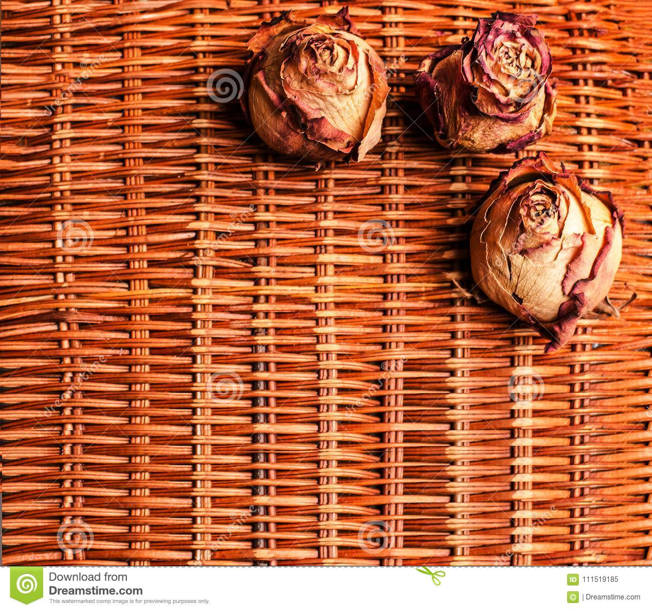 A rattan background with three dried roses.