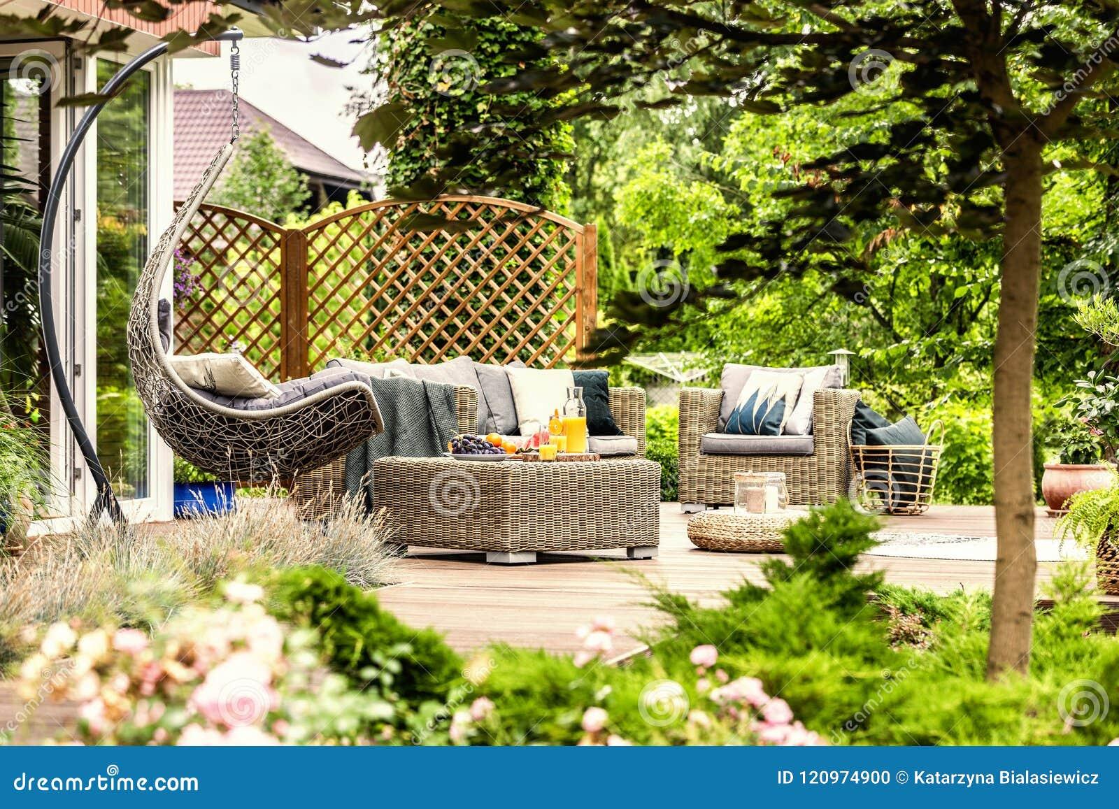 Marvelous Rattan Garden Furniture And Hanging Chair On Wooden Terrace Download Free Architecture Designs Ferenbritishbridgeorg