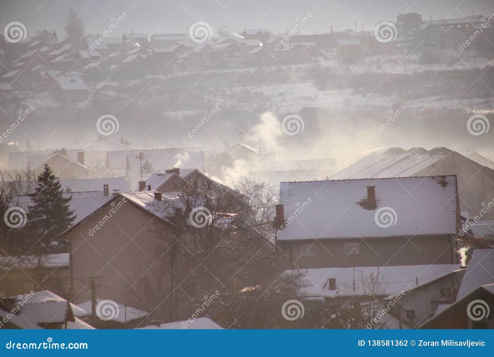 Rauchende Schlote an den Dächern mit Schnee von Häusern strahlen Rauch, Smog bei Sonnenaufgang, Schadstoffe eintragen Atmosphäre