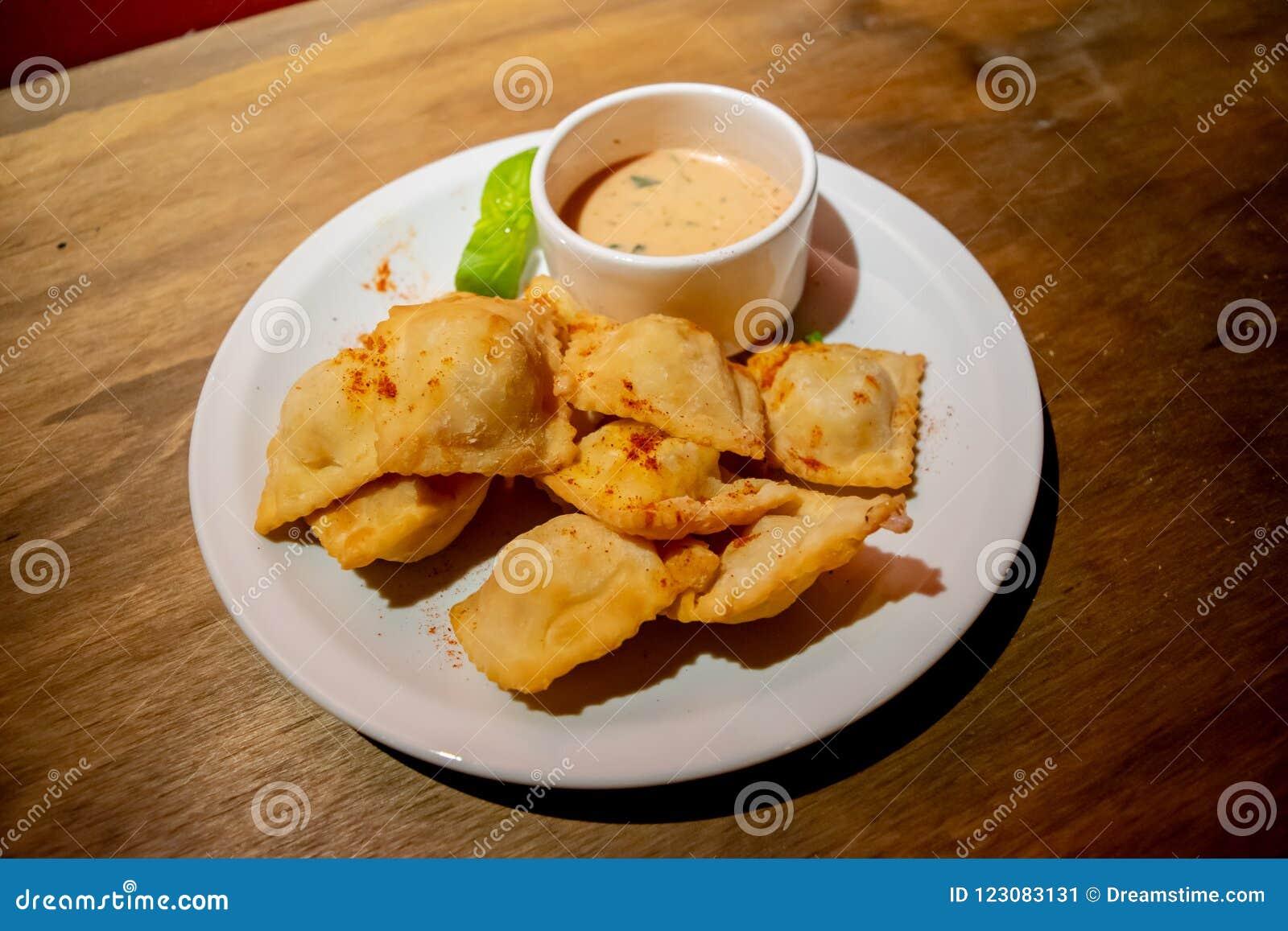 Raviolis fritos rellenos con el pollo y cebolletas