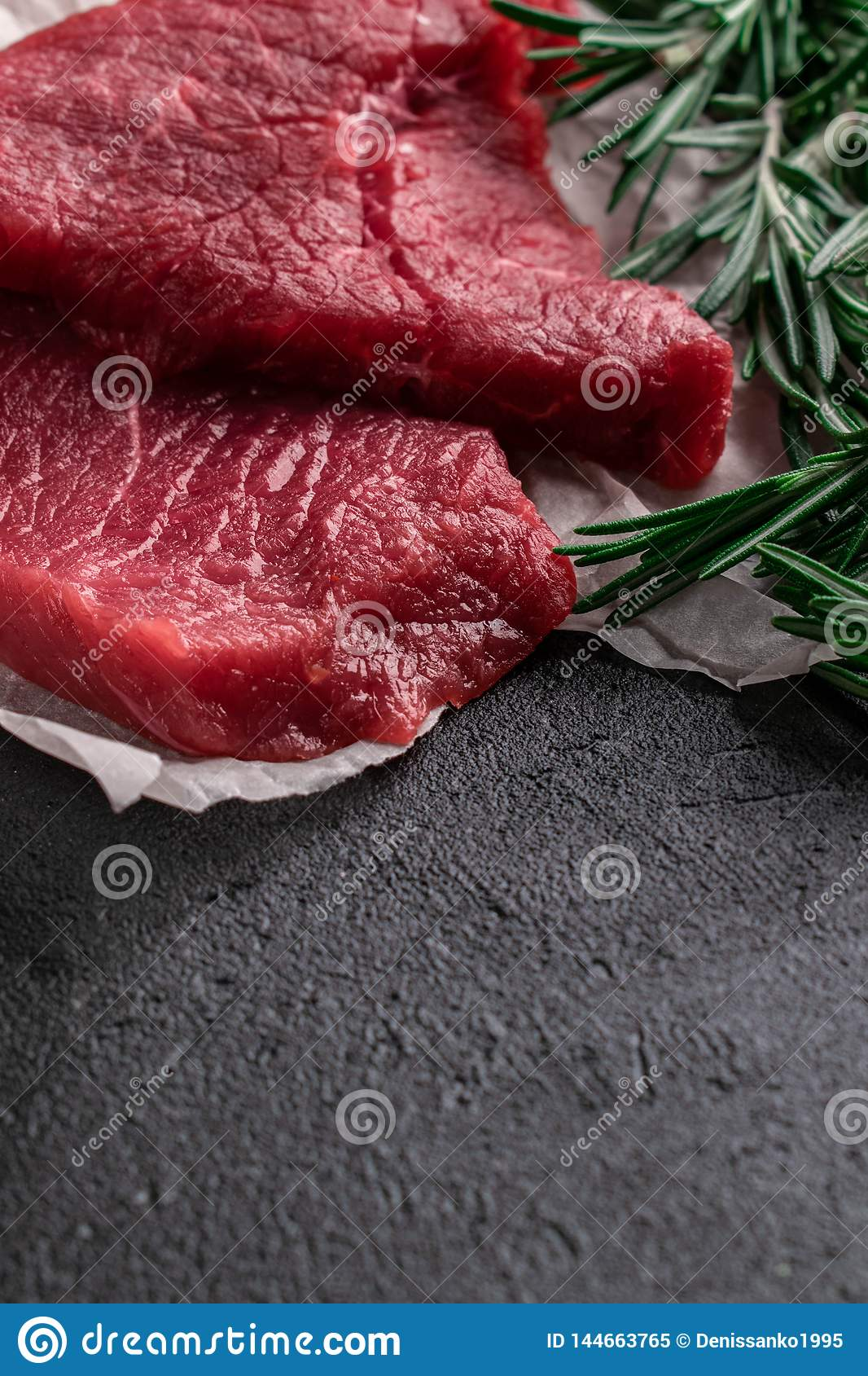 Raw beef steak with fresh branches rosemary on black background