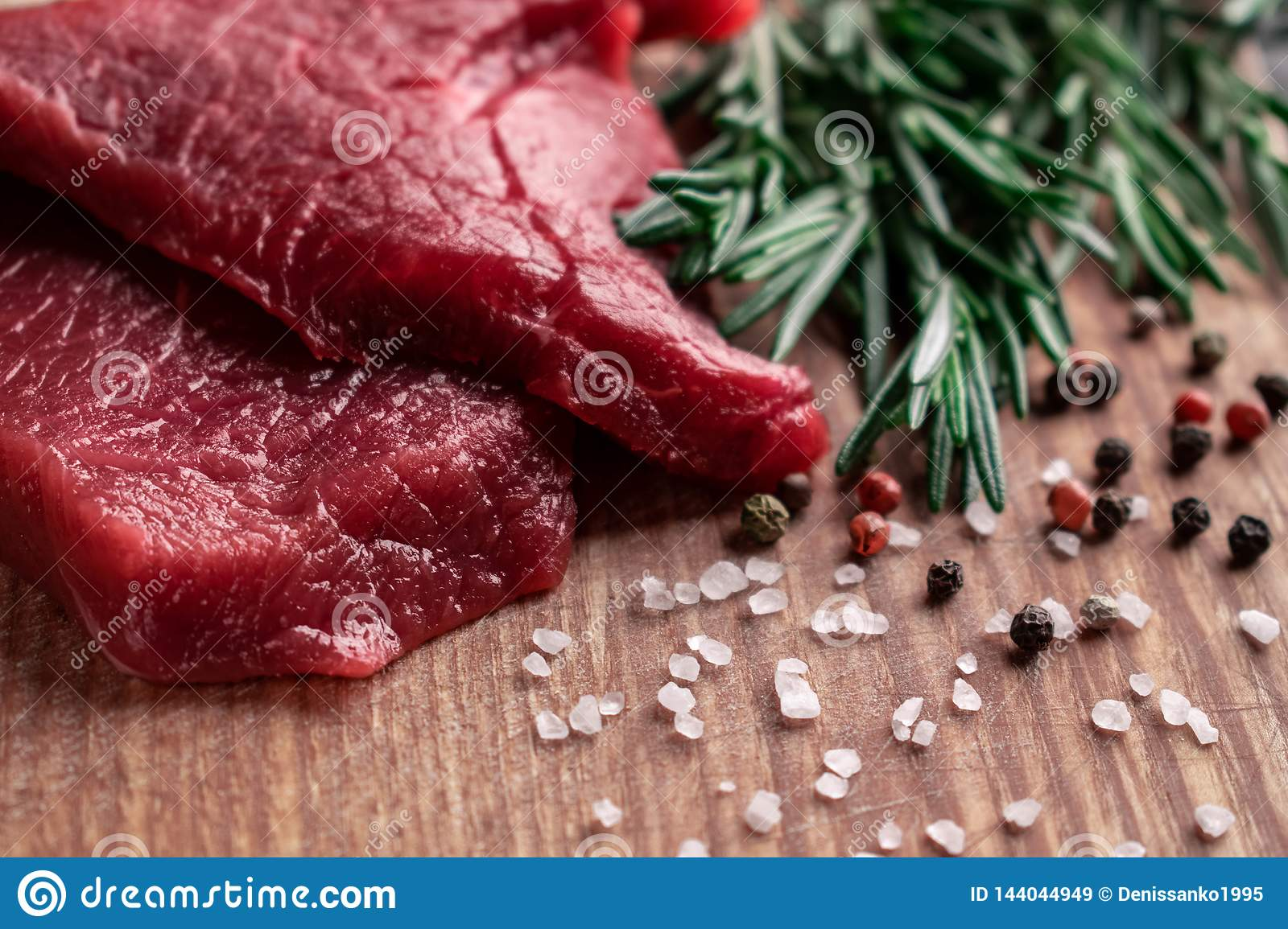 Raw beef steak with rosemary black, red pepper and coarse sea salt