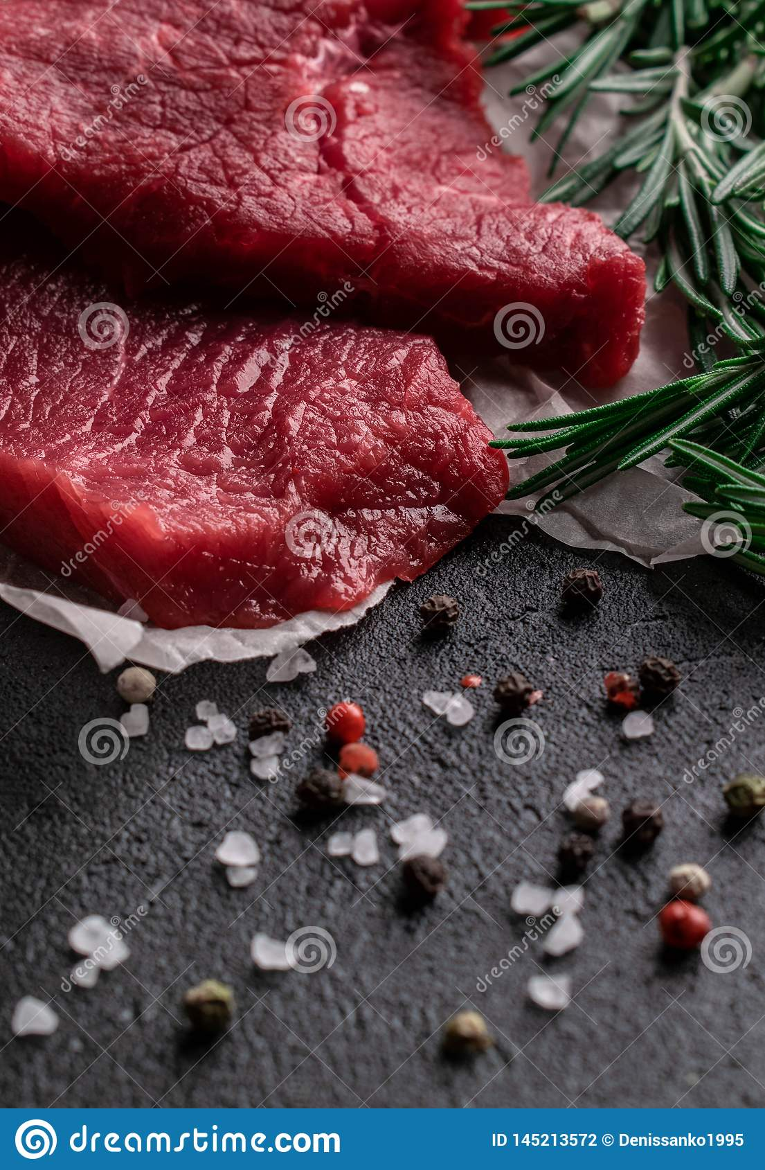 Raw beef steak with rosemary branches on parchment paper with pepper and salt