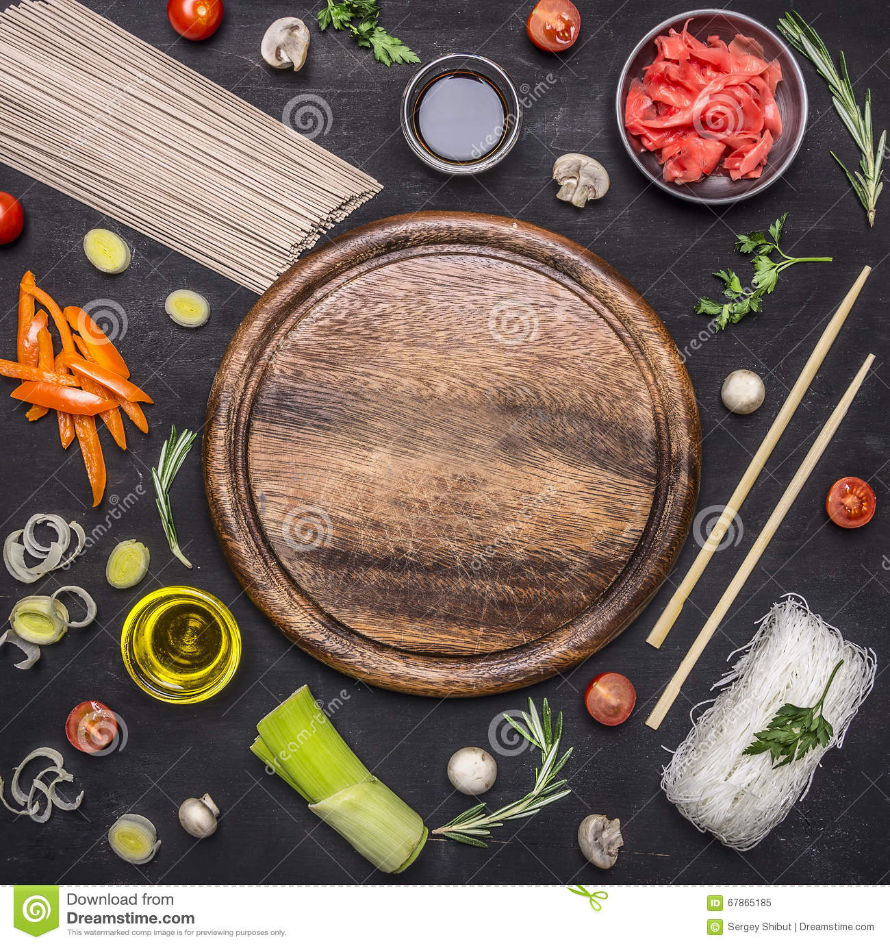 Raw buckwheat noodles with vegetables, ginger, chopsticks and ingredients, laid out around cutting board place for text,frame