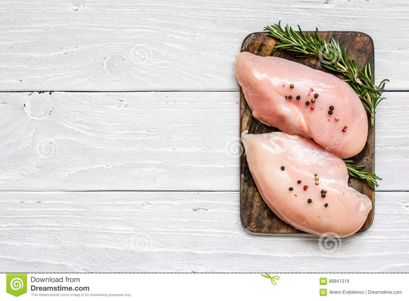 Raw chicken breast fillets on wooden cutting board with herbs and spices