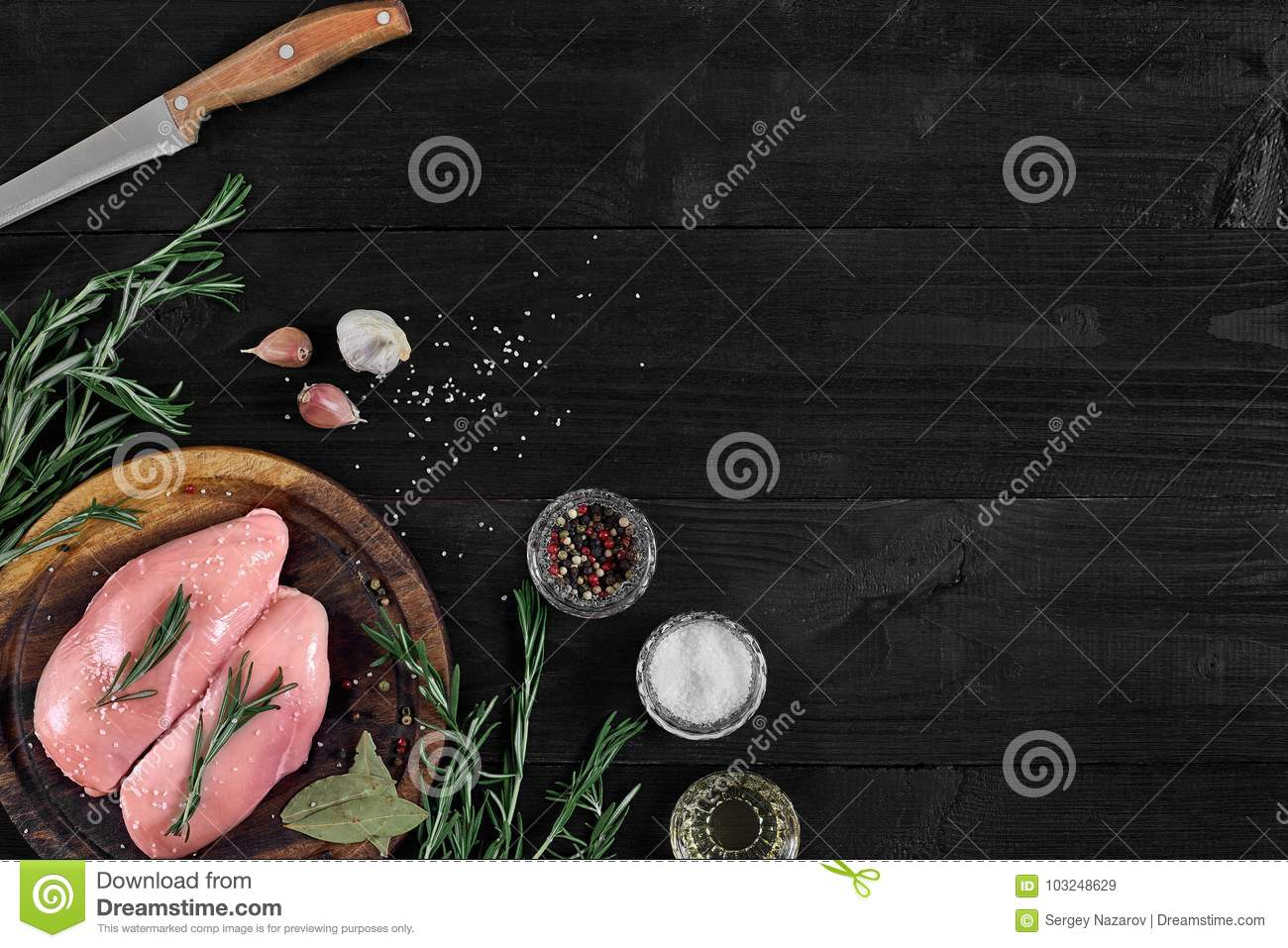 Raw chicken breast fillets on wooden cutting board with herbs and spices. Top view with copy space