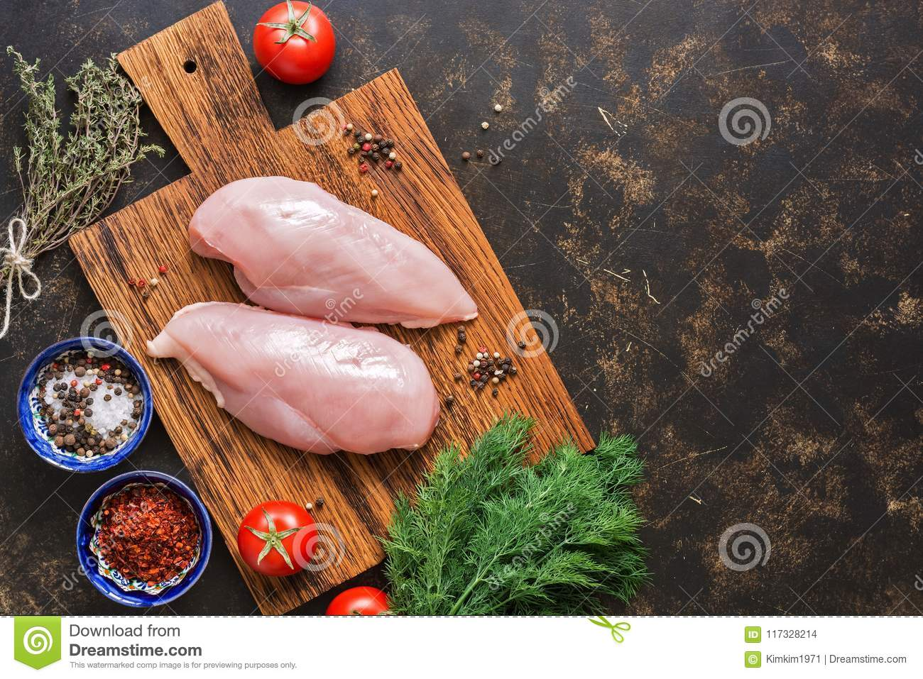 Raw chicken fillet on a cutting board with spices on a dark background. Top view, copy space, flat lay.