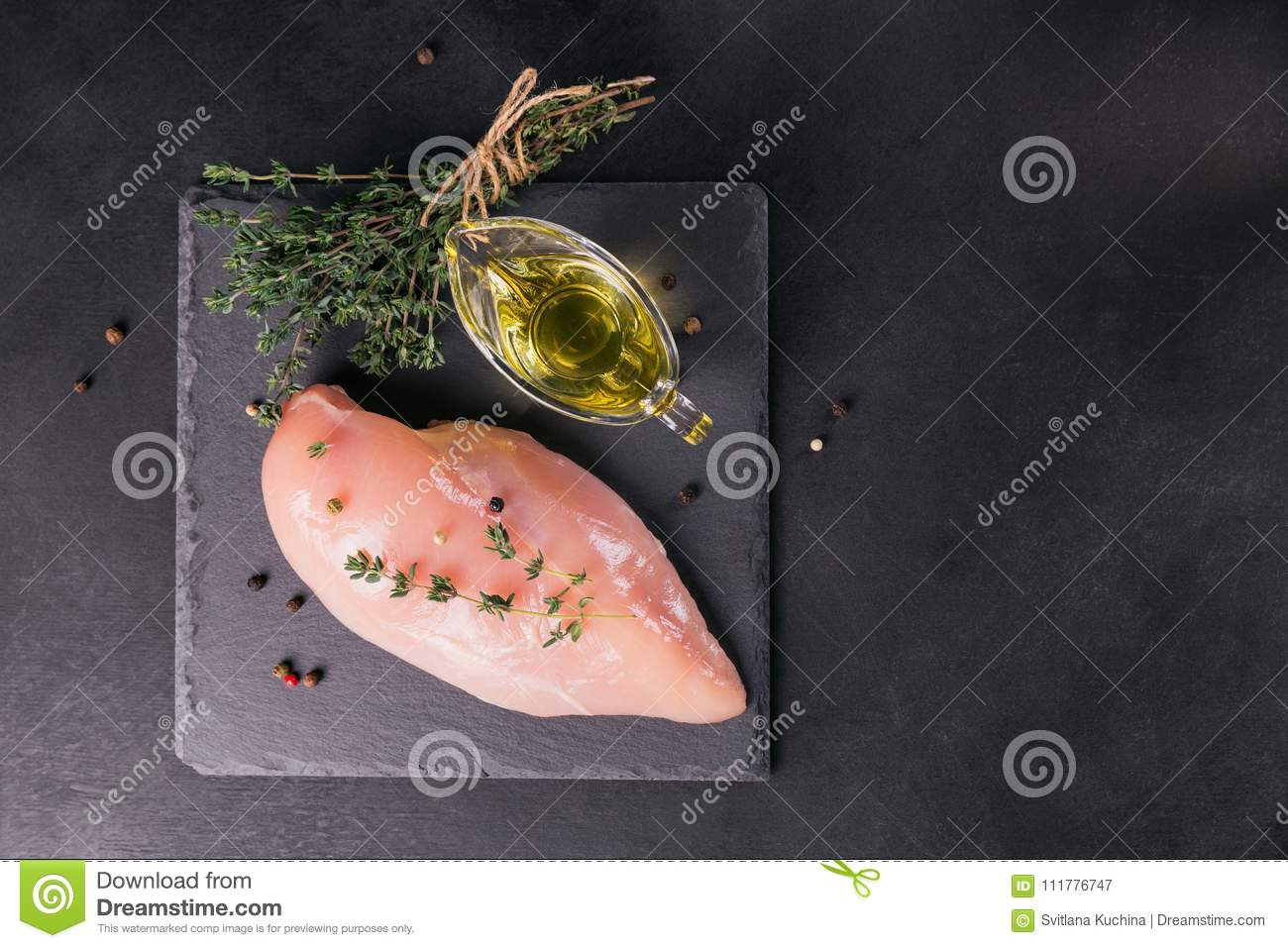 Raw chicken fillets with spices and herbs.