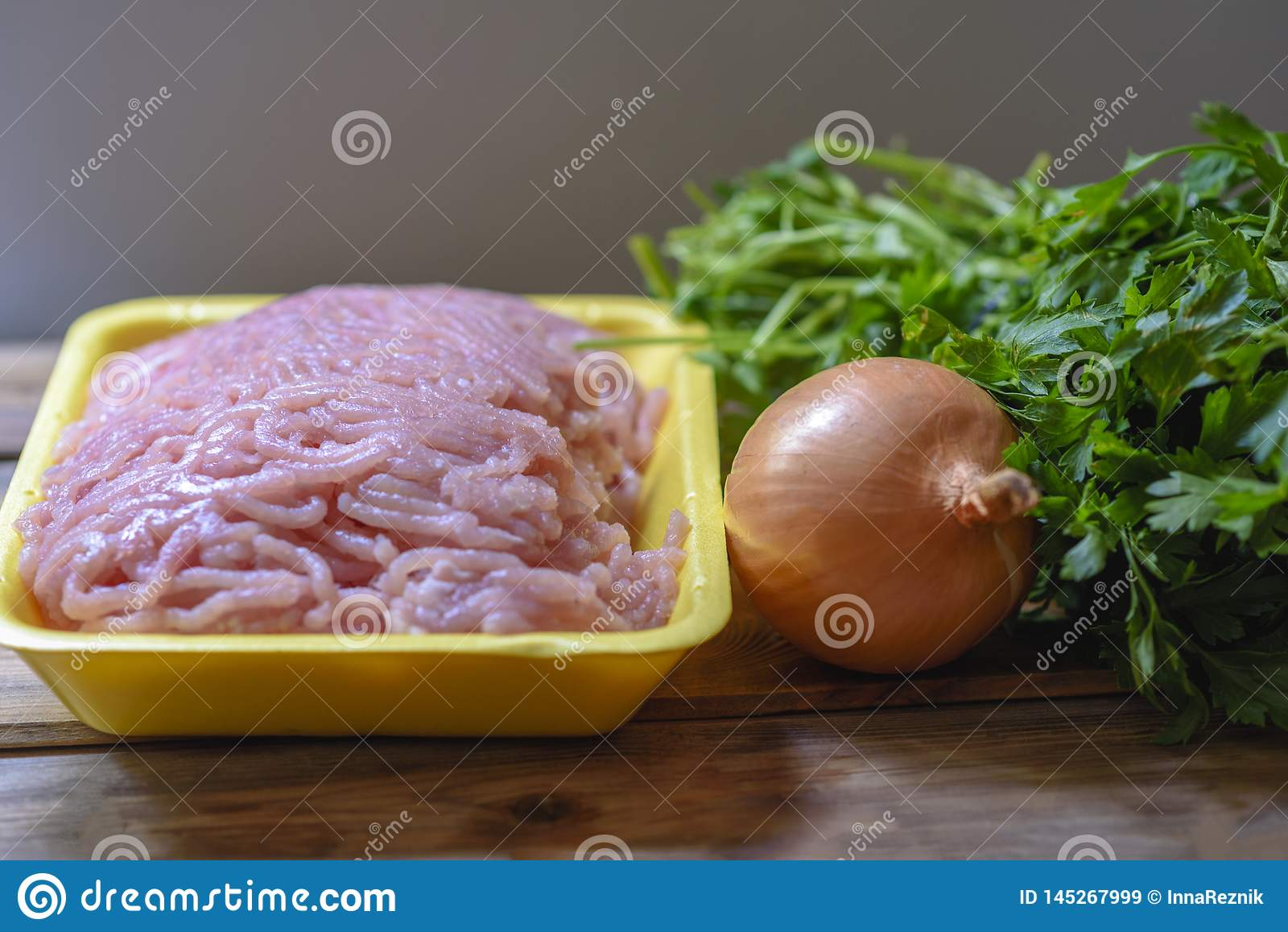 Raw chopped chicken meat, fresh parsley and onion.
