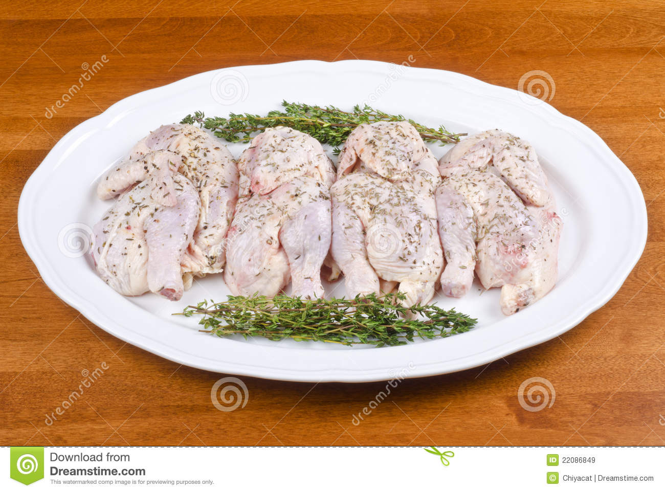 Raw Cornish Game Hen on a White Plate