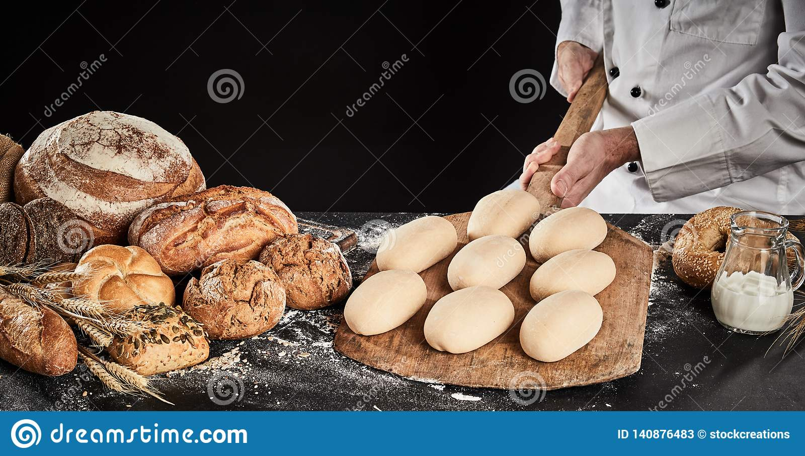 Raw dough for loaves of bread on a wooden paddle
