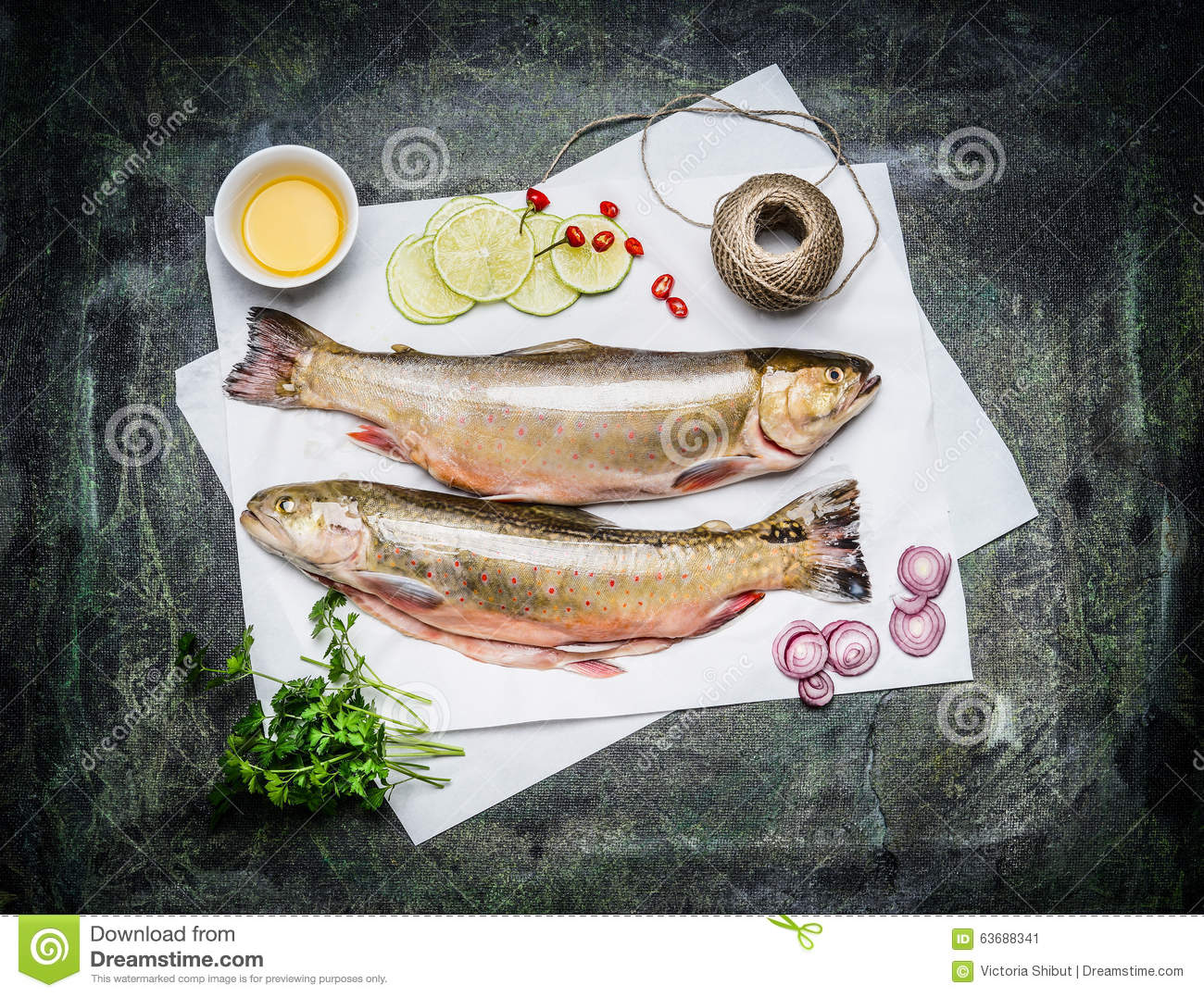 Raw fish on white paper with ingredients for cooking top for Cooking white fish