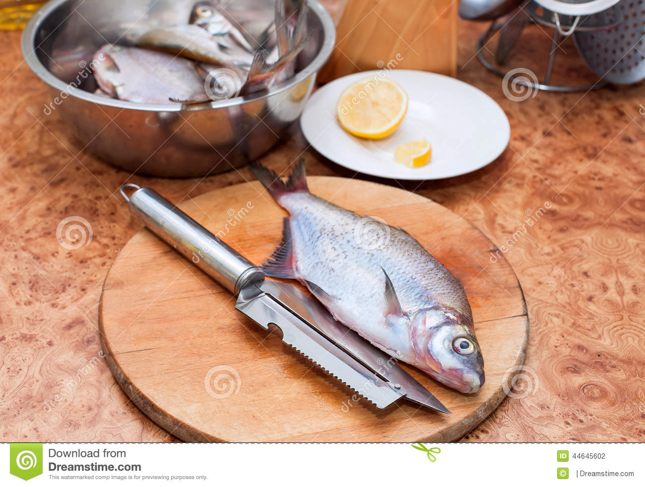 Raw fish on wooden cutting board with knife in the kitchen for Fish cutting board