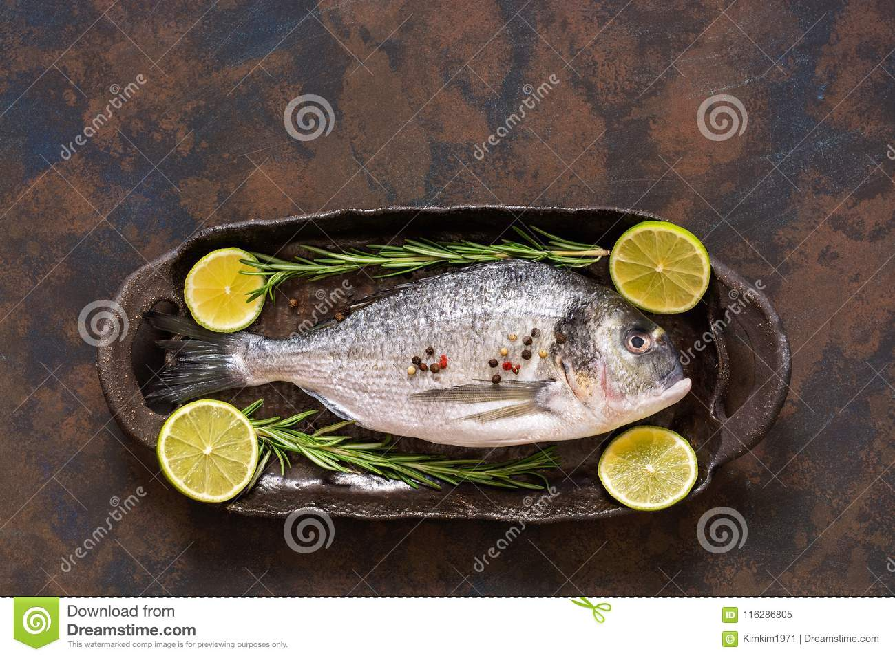Raw fresh fish with lime slices and rosemary. A top view, a place for your text or advertising.