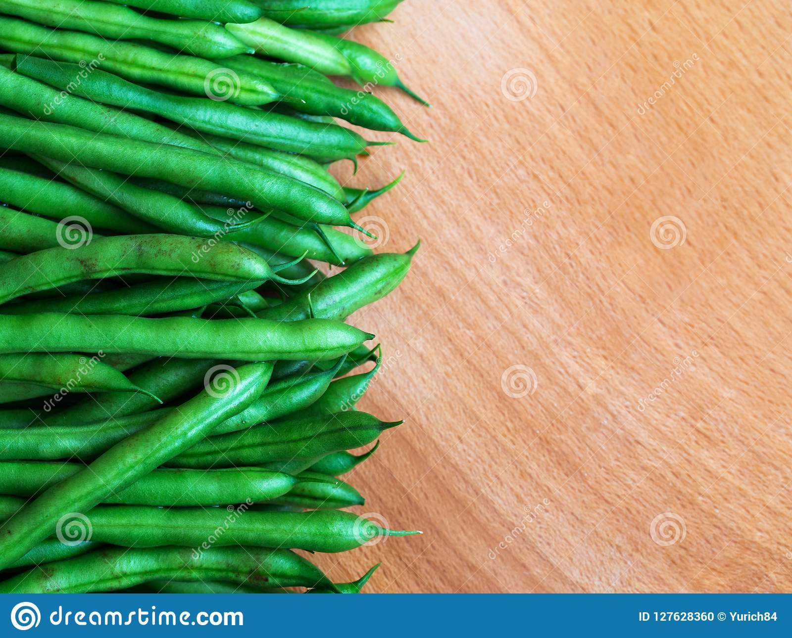 Raw green beans on wood background, close up, top view, copyspace