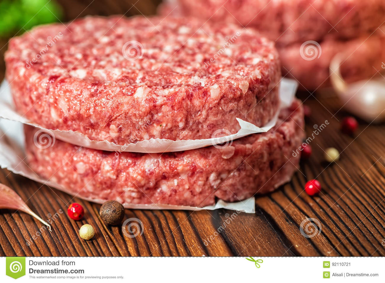 Raw ground beef meat hamburger patties on paper, dry pepper