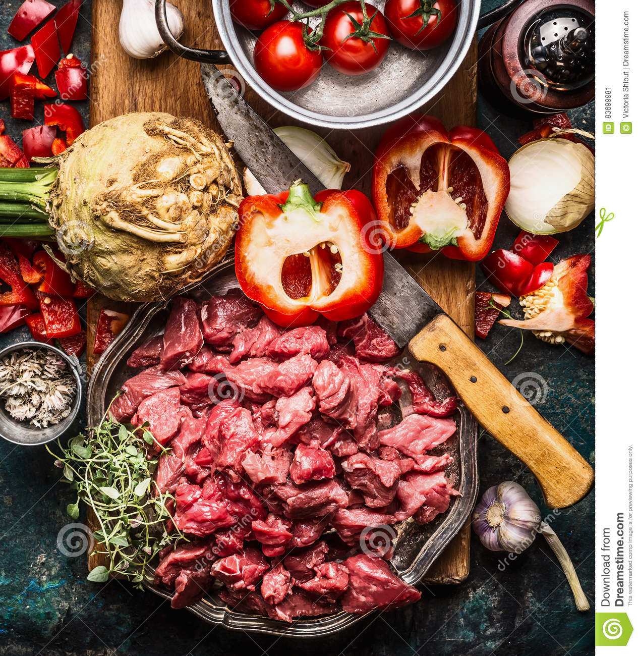 Raw gut meat with kitchen knife fresh vegetables, seasoning and spices for tasty cooking on dark rustic background
