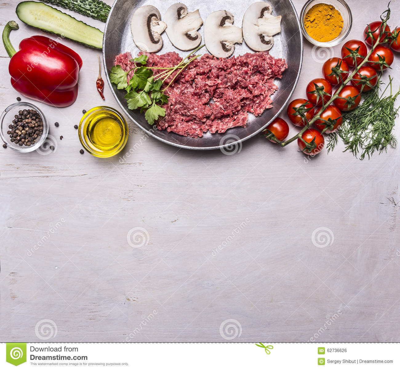 Raw minced meat with mushrooms in a pan, pepper, tomatoes on a branch, spices, cucumbers border ,text area, on wooden rustic