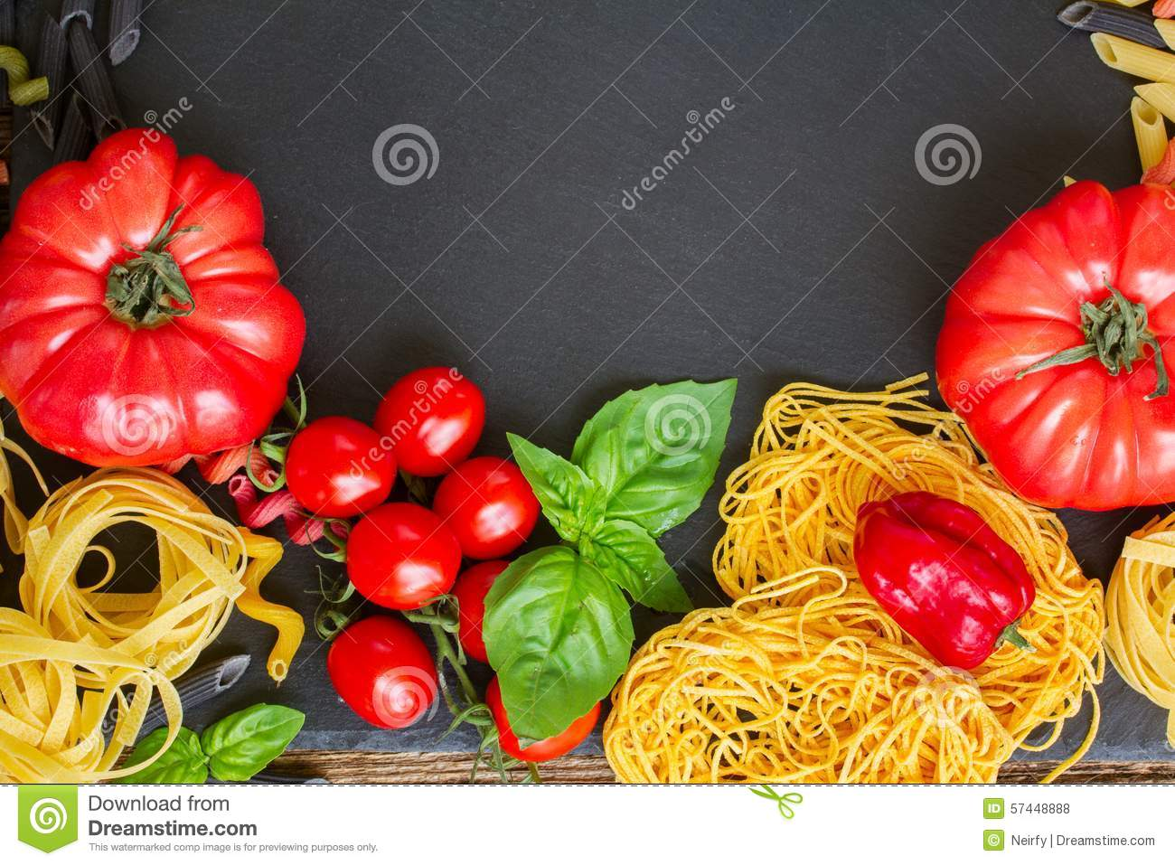 Raw pasta with ingridients on black board
