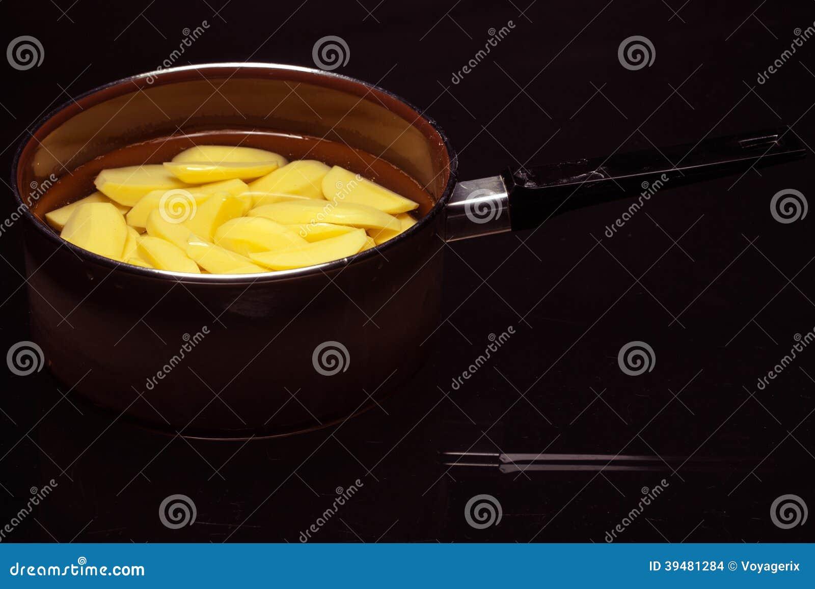 Raw peeled potatoes in pot pan on black. Healthy food.