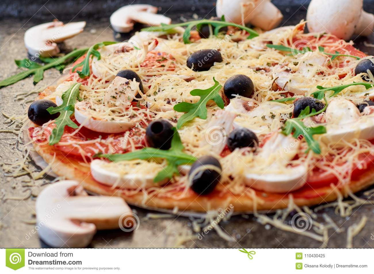 Raw pizza on the black background close up. Vegetarian pizza with cheese, vegetables, mushrooms, black olives and fresh rucola