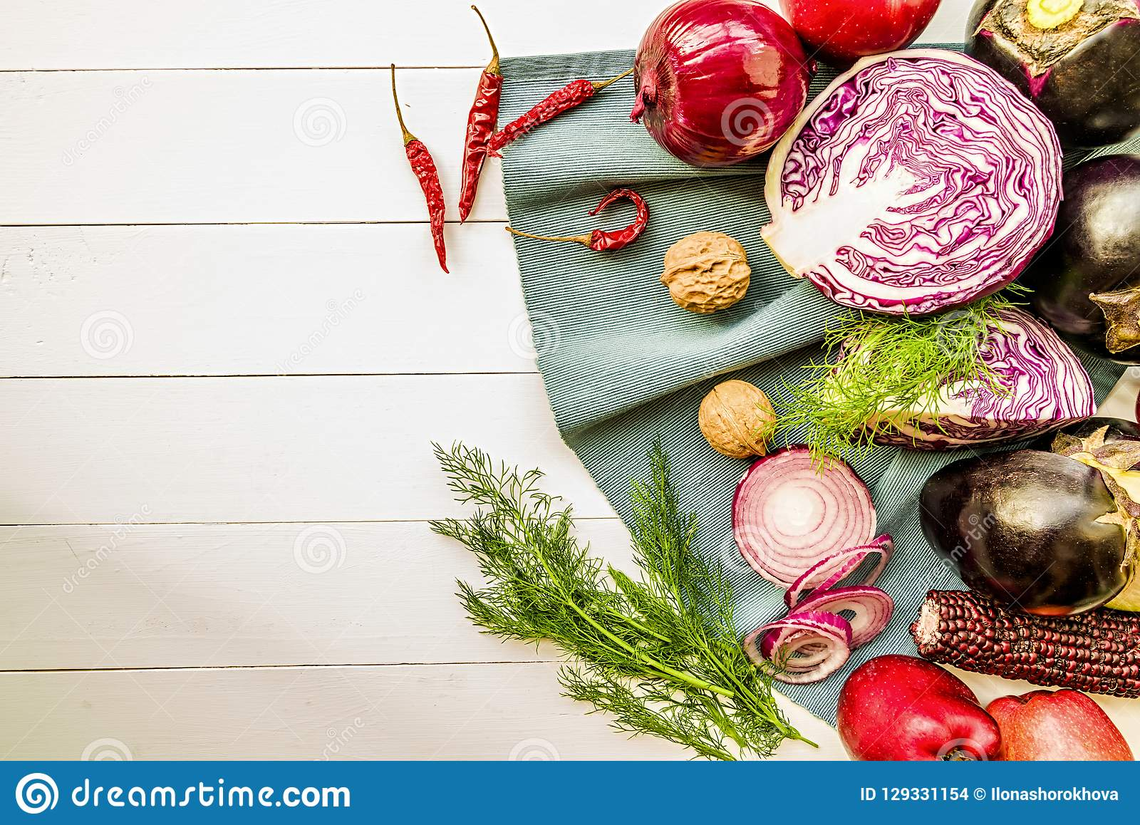 Raw purple vegetables and fruit on white wooden background with copy space top view. Raw purple veggies and fruit: eggplants, cabbage, onions, apples, walnuts stock images