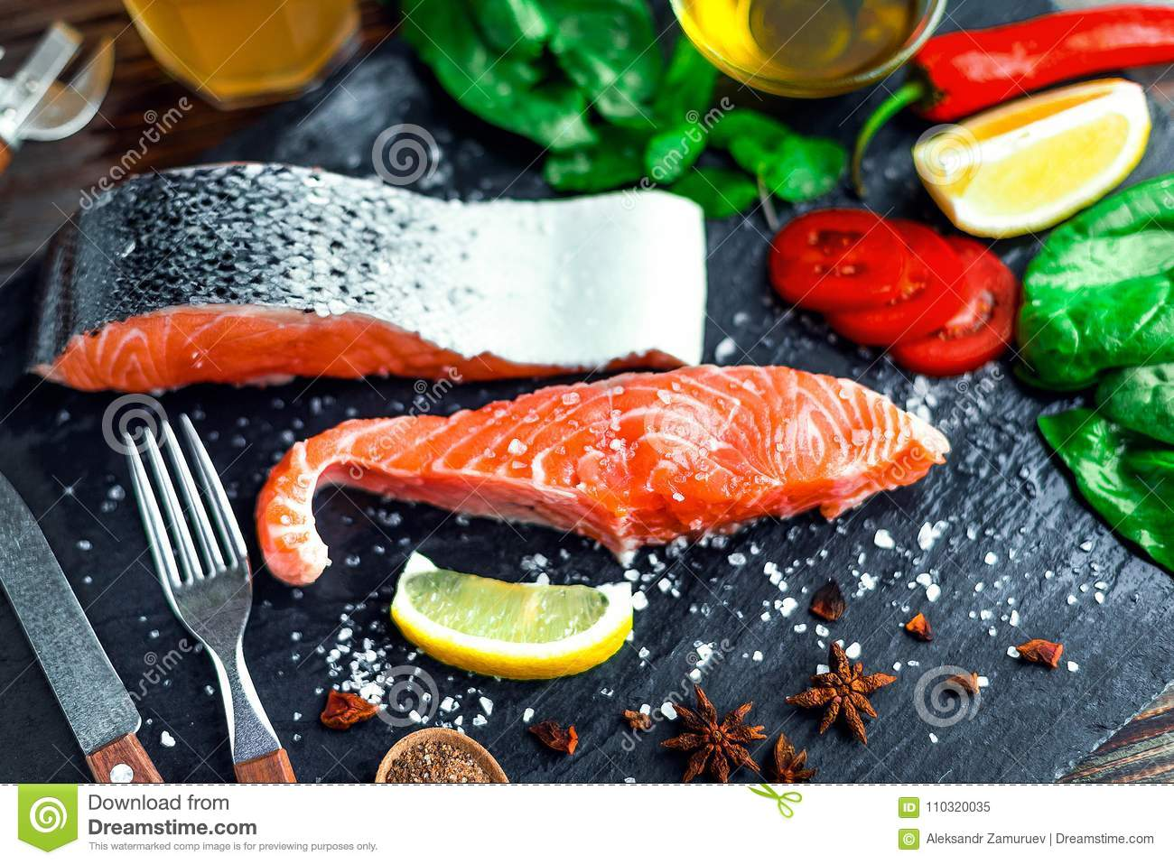 Raw Salmon Fillet And Ingredients For Cooking On A Dark Background