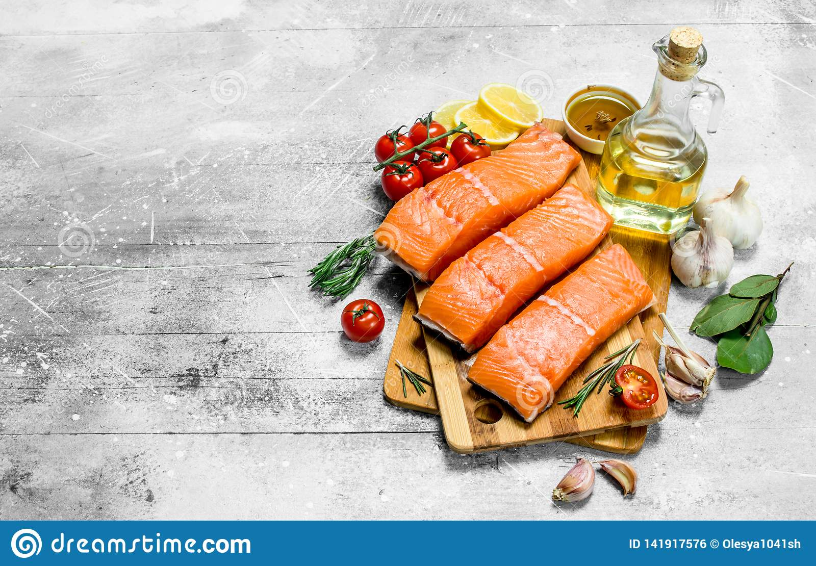 Raw salmon fish filet with spices, herbs and ripe tomatoes