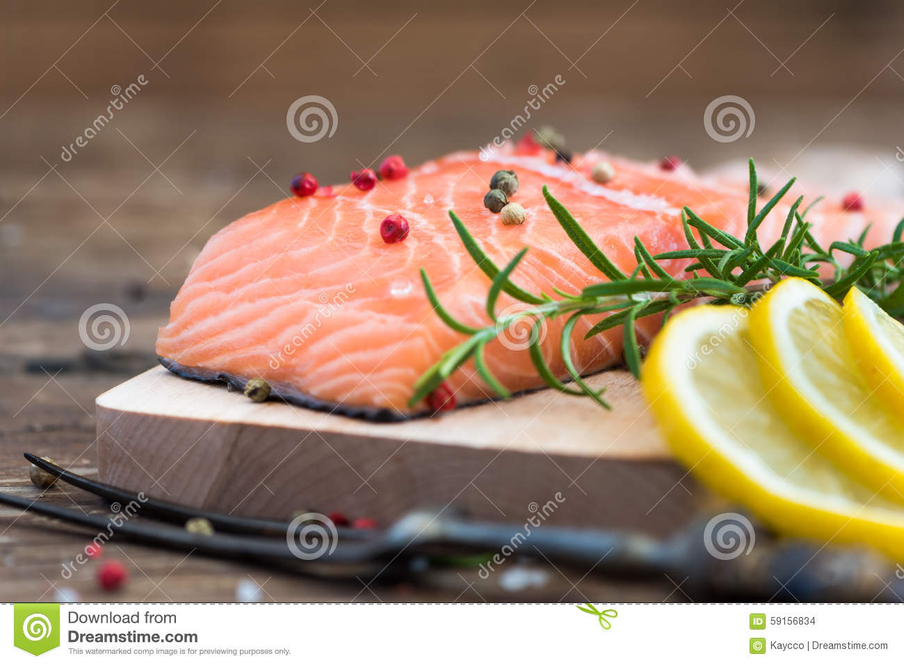 Raw salmon fish fillet with lemon and fresh herbs stock for Fish fillet board