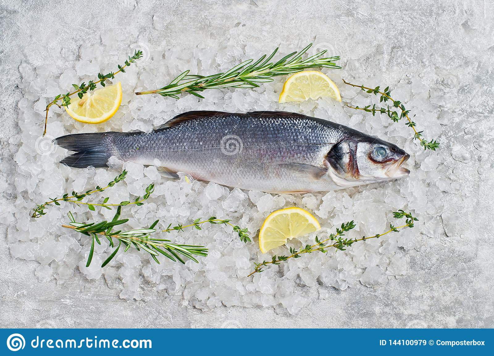 Raw sea bass on ice with rosemary, thyme and lemon. Gray background, top view.