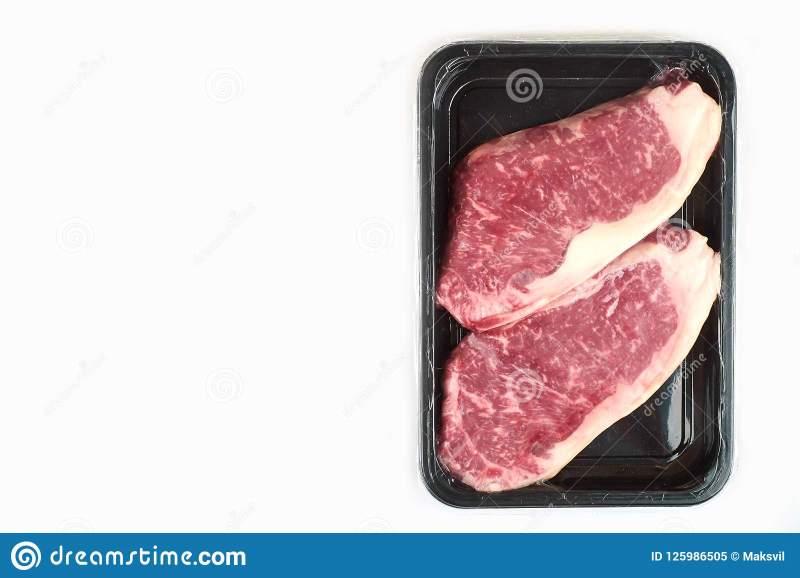 Raw steak in an airtight vacuum package on a white background.